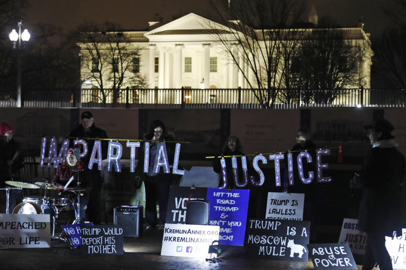 Protesters display signs and sing in front of the White House in Washington, Tuesday, Jan. 14, 2020. (AP Photo/Steve Helber)