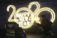 A woman poses for photos to celebrate the upcoming New Year in Seoul, South Korea, Tuesday, Dec. 31, 2019. (AP Photo/Ahn Young-joon)