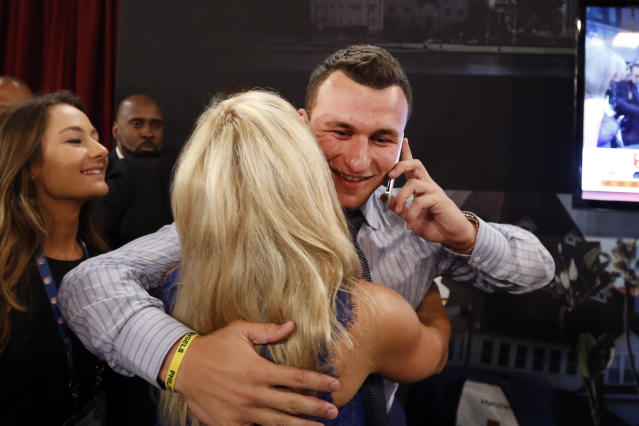 Johnny Manziel, from Texas A&M, reacts after being selected 22nd overall by the Cleveland Browns during the first round of the NFL football draft, Thursday, May 8, 2014, at Radio City Music Hall in New York. (AP Photo/Jason DeCrow)