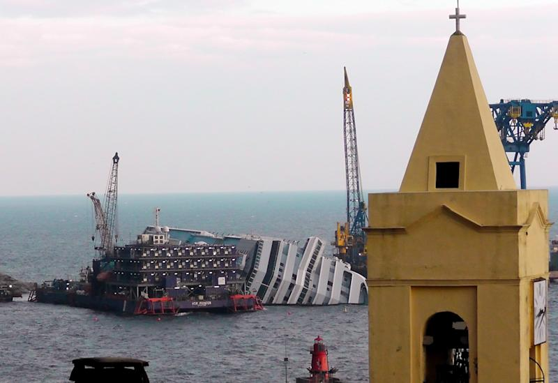 """FILE - This Jan. 11, 2013 file photo shows the cruise ship Costa Concordia leaning on its side, near the shore of the Tuscan island of Giglio, Italy.  Thirty-two people died when the ship ran aground on Jan. 13, 2012. Cruise watchers looking back at the industry's past year say the Concordia disaster affected everything from prices to safety drills to first-time cruisers, but bookings appear to be picking up as the 2013 cruise booking season gets under way. The first three months of each year are known as """"wave season,""""a period when many cruisers book trips as they plan ahead for summer vacations.  (AP Photo/Paolo Santalucia, file)"""