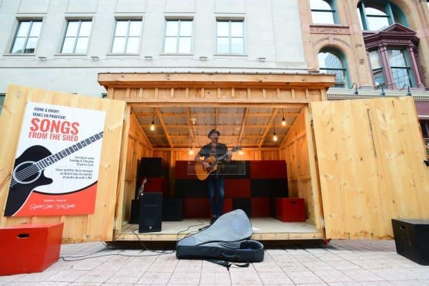 Ottawa musician Shawn Tavenier performs from behind a sheet of plexiglass on Sparks Street last summer. On Friday, the Ontario government announced $2.5 million in funding to support the province's struggling music industry. (Sean Kilpatrick/Canadian Press - image credit)