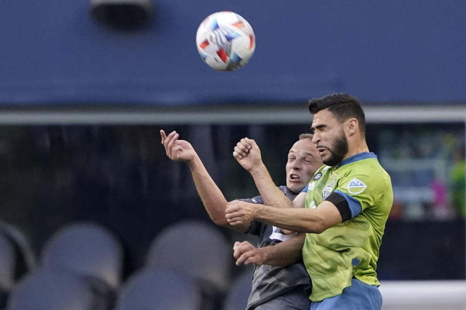 Seattle Sounders midfielder Alex Roldan, right, and Minnesota United defender Chase Gasper, left, vie for a header during the first half of an MLS soccer match Friday, April 16, 2021, in Seattle. (AP Photo/Ted S. Warren)