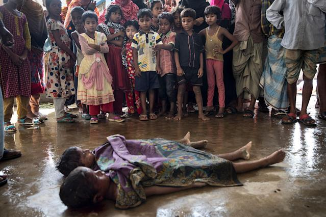 <p>SEPT. 29, 2017 – Children watch in Inani , Bangladesh, as the bodies of children are prepared for the funeral after a boat sunk in rough seas off the coast of Bangladesh carrying over 100 people . Seventeen survivors were found along with the bodies of 20 women and children with over 50 missing. Over a half a million Rohingya refugees have fled into Bangladesh from the horrific violence in Rakhine state in Myanmar causing a humanitarian crisis. (Photo: Paula Bronstein/Getty Images) </p>