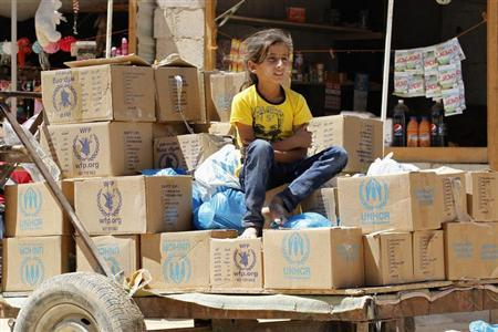 A Syrian refugee girl sits on humanitarian aid boxes at Al Zaatri refugee camp