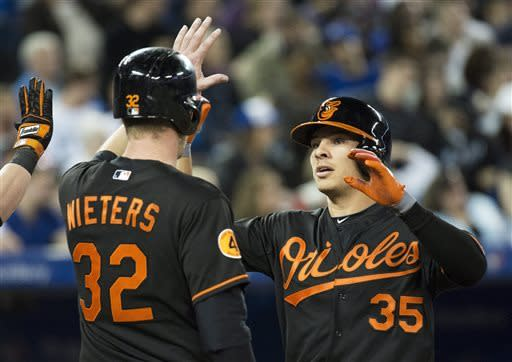 Baltimore Orioles DH Danny Valencia, right, celebrates his two-run home run with teammate Matt Wieters, left, while playing against the Toronto Blue Jays during third-inning AL baseball game action in Toronto, Friday May 24, 2013. (AP Photo/The Canadian Press, Nathan Denette)