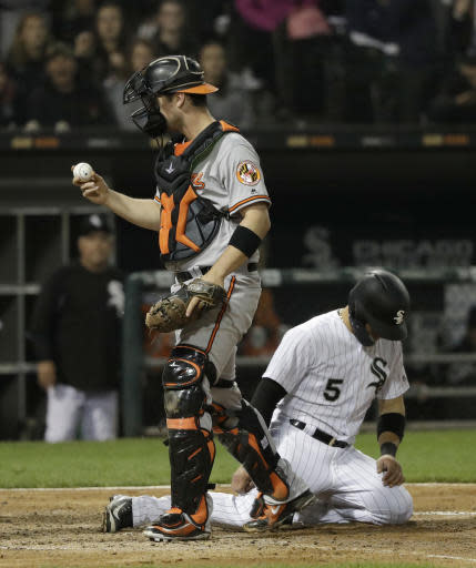 Baltimore Orioles catcher Andrew Susac, left, walks back to the dugout after tagging out Chicago White Sox's Yolmer Sanchez at home during the fifth inning of a baseball game Monday, May 21, 2018, in Chicago. (AP Photo/Charles Rex Arbogast)
