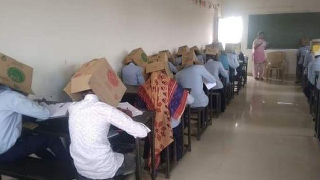 Pupils were forced to wear cardboard boxes on their heads in a bid to stop them cheating during a chemistry exam at Bhagat Pre-University College in Haveri, Karnataka state. (Twitter/BBC)