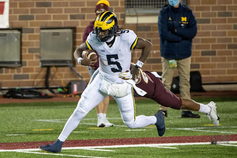 Michigan Wolverines quarterback Joe Milton rushes with the ball for a first down in the first half against Minnesota at TCF Bank Stadium, Oct. 24, 2020.