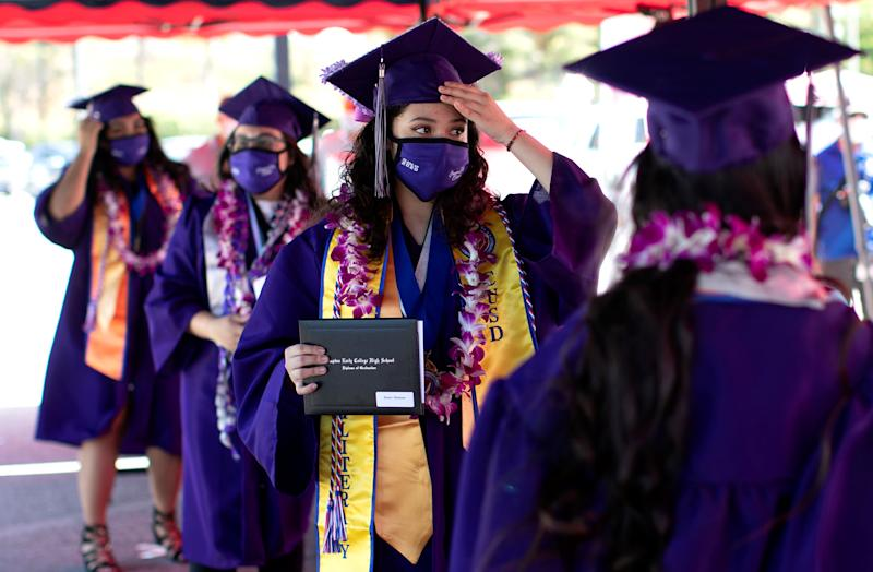 Compton Early College High School graduating student Chelsea Donis adjust her mortar after picking up her diploma in a parking lot during a drive-thru graduating ceremony, during the outbreak of the coronavirus disease (COVID-19) in Compton, California U.S. June 10, 2020. REUTERS/Mario Anzuoni