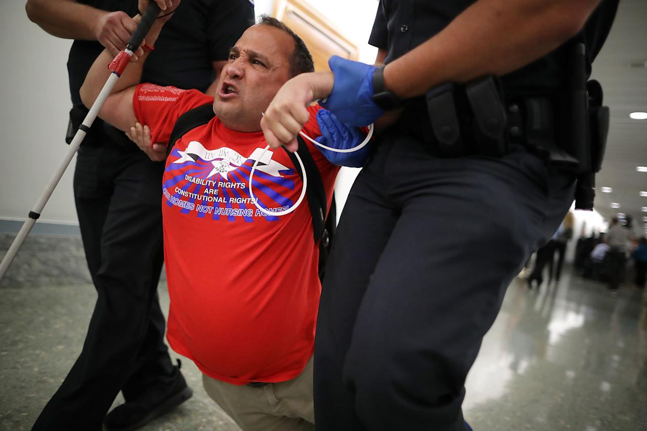 <p>U.S. Capitol Police drag a blind protester out of a Senate Finance Committee hearing about the proposed Graham-Cassidy Healthcare Bill in the Dirksen Senate Office Building on Capitol Hill September 25, 2017 in Washington, DC. Demonstrators disrupted the hearing to protest the legislation, the next in a series of Republican proposals to replace the Affordable Care Act, also called Obamacare. (Photo: Chip Somodevilla/Getty Images) </p>