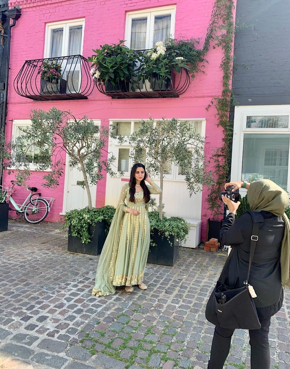 Beauty influencer Gulshan shoots outfit photos outside of the pink house on St. Lukes Mews.