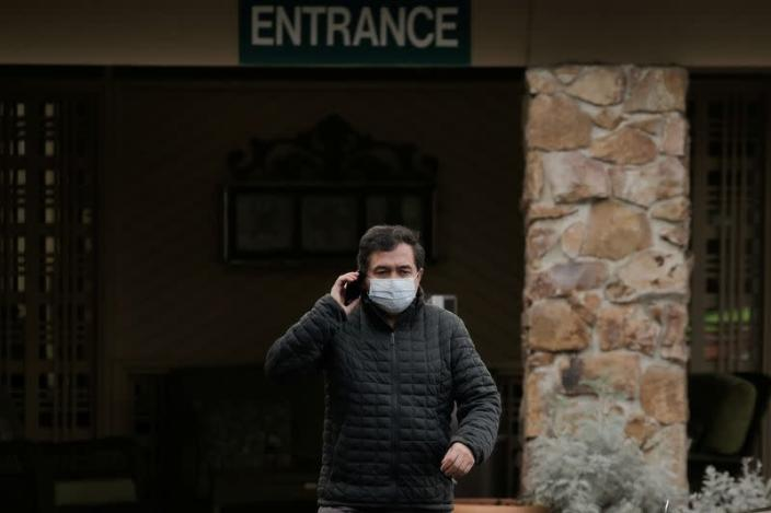 A man wears a mask while leaving the Life Care Center of Kirkland, where two of three confirmed coronavirus cases in the state had links to the long-term care facility in Kirkland