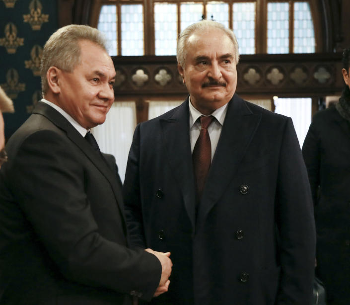 In this handout photo released by Russian Foreign Ministry Press Service, Russian Defense Minister Sergei Shoigu, left, shakes hands with Khalifa Hifter, the head of the self-styled Libyan National Army prior to the talks in Moscow, Russia, Monday, Jan. 13, 2020. Foreign and defense ministers of Russia and Turkey met as part of an effort by Moscow and Ankara to sponsor Monday's talks between rival parties in Libya in the Russian capital. (Russian Foreign Ministry Press Service via AP)