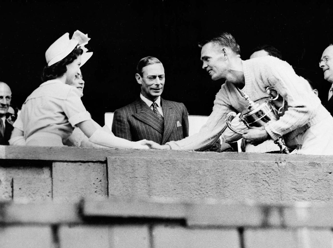 Jack Kramer of the U.S. holds his trophy as he shakes hands with Princess Margaret Rose after winning the men's singles championship at Wimbledon, July 4, 1947.  Almost hidden by the Princess is Queen Elizabeth and King George is at center.  (AP Photo)