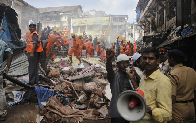 <p>A rescue worker makes an announcement on a loudspeaker at the site of a building collapse in Mumbai, India, Aug. 31, 2017. (Photo: Rafiq Maqbool/AP) </p>