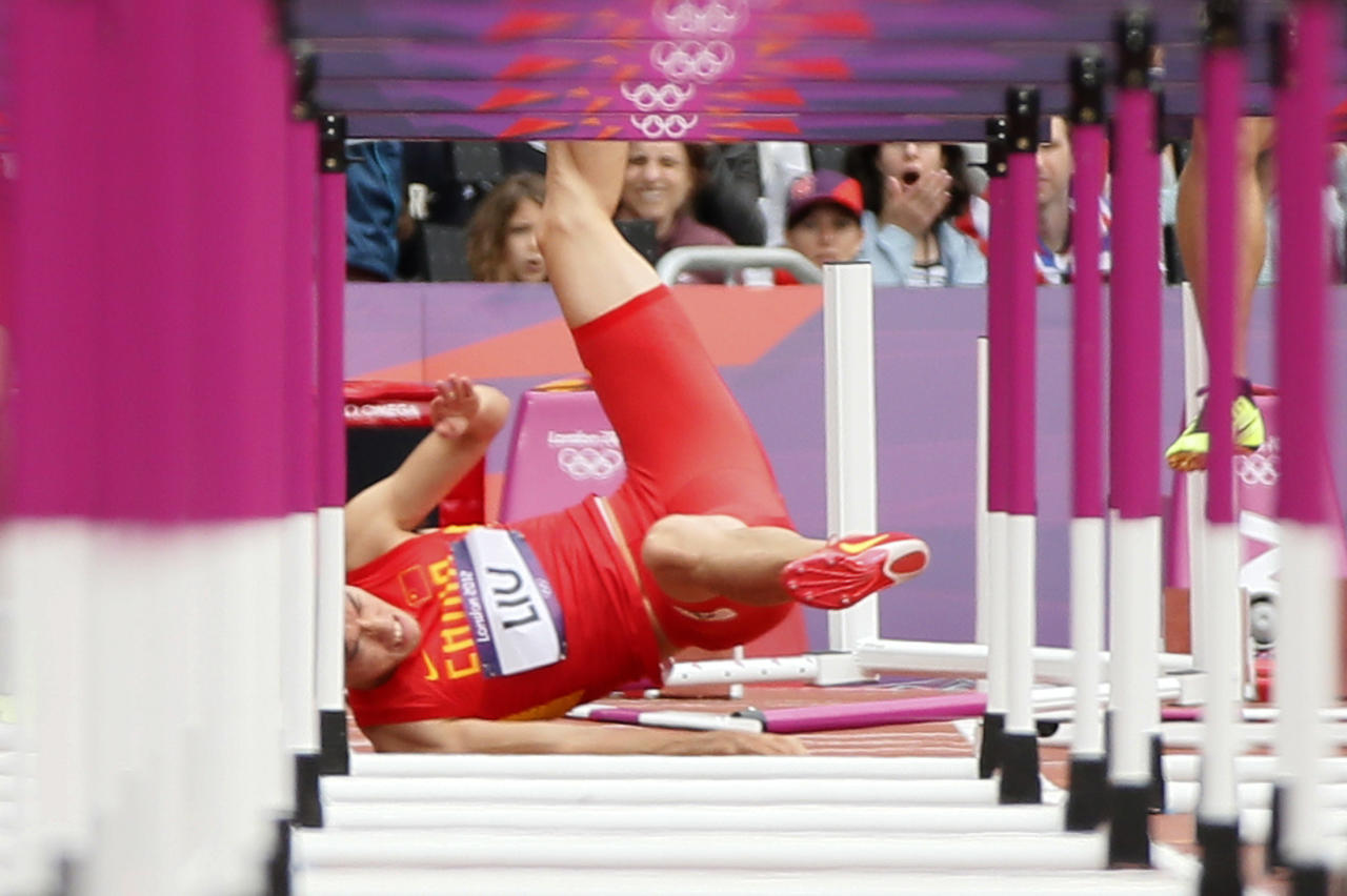 China's Liu Xiang falls after crashing into the first hurdle during his men's 110m hurdles round 1 heat at the London 2012 Olympic Games at the Olympic Stadium August 7, 2012. REUTERS/Lucy Nicholson (BRITAIN  - Tags: OLYMPICS SPORT ATHLETICS TPX IMAGES OF THE DAY)