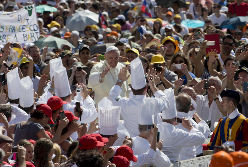Pope Francis salutes a group of professional cooks as he arrives in St. Peter's square at the Vatican for his weekly general audience Wednesday, June 26, 2013. (AP Photo/Alessandra Tarantino)
