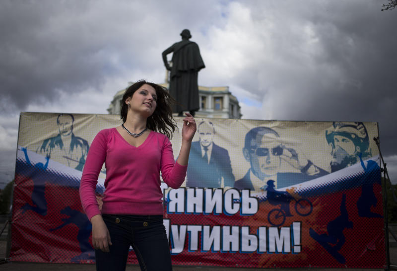 "An activist of the Pro-Kremlin youth movement, Mestnye (locals), dances in front of a poster reading ""Tighten with Putin"" celebrating the 60th birthday of Russian President Vladimir Putin in Moscow, Sunday, Oct. 7, 2012, with the statue of Alexander Suvorov in the background. Vladimir Putin turns 60-years old on Sunday, Oct. 7, 2012, and has recently sought to demonstrate his youthful vigor by many personal endeavors, but while he has shown creativity in his action-man stunts, the Russian president seems surprisingly vulnerable to the vagaries of oil prices.(AP Photo/Alexander Zemlianichenko)"