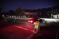 FILE - In this Oct. 10, 2019, file photo, a car drives through a darkened Montclair Village as Pacific Gas & Electric power shutdowns continue in Oakland, Calif. When Pacific Gas & Electric set up emergency operations centers to coordinate intentional blackouts intended to prevent wildfires in Northern California, the nation's largest utility forgot one thing, emergency managers who knew the fundamentals of emergency management in California. (AP Photo/Noah Berger, File)