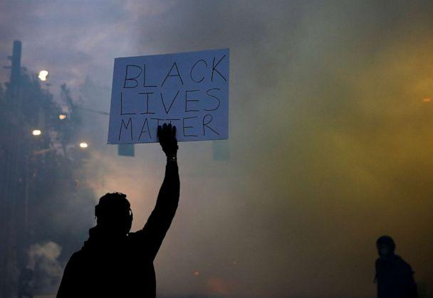 PHOTO: A person holds a 'Black Lives Matter' sign as as a heavy cloud of tear gas and smoke rises after being deployed by Seattle police as protesters rally against the death in Minneapolis police custody of George Floyd, in Seattle, June 1, 2020. (Lindsey Wasson/Reuters, FILE)