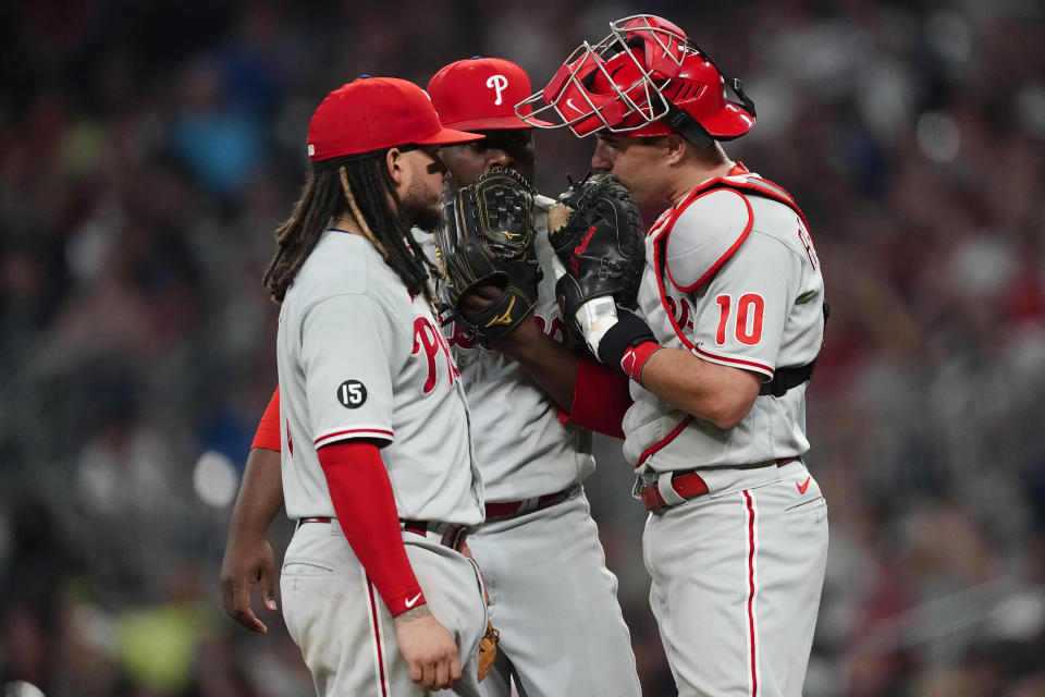 Philadelphia Phillies' Freddy Galvis, left,, Hector Neris (50) and catcher J.T. Realmuto (10) meet on the mound during the eighth inning of a baseball game against the Atlanta Braves Tuesday, Sept. 28, 2021, in Atlanta. (AP Photo/John Bazemore)