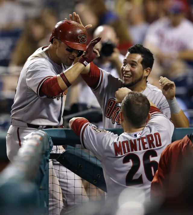 Arizona Diamondbacks' Martin Prado, left, celebrates with teammates after hitting a go-ahead RBI-sacrifice fly during the 10th inning of a baseball game against the Philadelphia Phillies, Saturday, July 26, 2014, in Philadelphia. Arizona won 10-6 in 10 innings. (AP Photo/Matt Slocum)