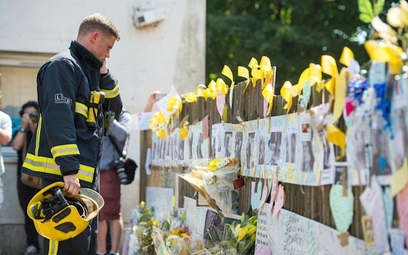 A firefighter views tributes after observing a minute's silence at Latymer Community Centre, near to Grenfell Tower - Credit: Dominic Lipinski/PA Wire