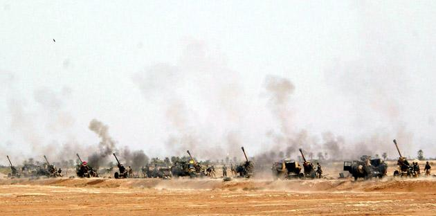 British soldiers from the 29 Commando Regiment Royal Artillery fire their 105mm guns as they push north through southern Iraq, 24 March 2003. British forces scoured the Iraqi desert for two missing soldiers 24 March but said the US-led war could weather setbacks hitting both the air and ground campaign.