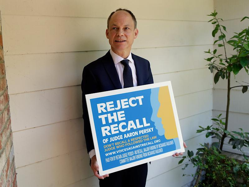 Judge Aaron Persky poses for a photo with a sign opposing his recall in Los Altos Hills, California: AP