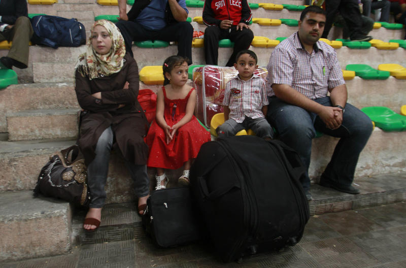 A Palestinian family wait for a bus to cross the border from Khan Younis Refugee Camp in Gaza to the El-Arish airport in Egypt to take their flight on Palestinian Airlines to Amman, Jordan, Sunday, May 27, 2012. Palestinian Airlines is back in the skies after being grounded for seven years by the vagaries of the Mideast conflict. It's a mom-and-pop operation, with just two 48-seat turbo-prop planes, two weekly flights and a borrowed hub in Egypt, but Palestinians say just being on the map again is what matters.(AP photo/Hatem Moussa)