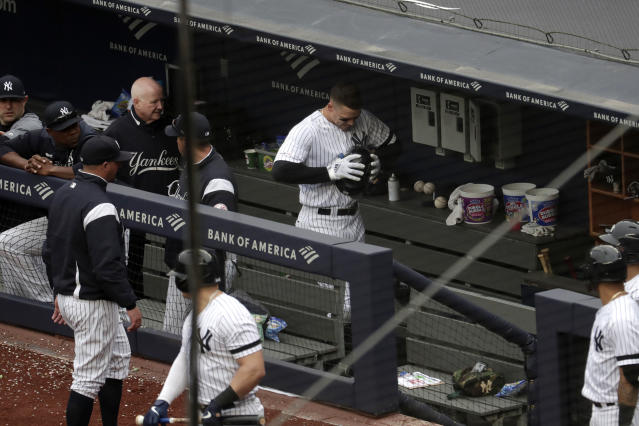 New York Yankees' Aaron Judge, center, clenches his helmet while walking in the dugout after he was pulled from the game after suffering an apparent injury while hitting a single off Kansas City Royals starting pitcher Glenn Sparkman during the sixth inning of a baseball game, Saturday, April 20, 2019, in New York. (AP Photo/Julio Cortez)