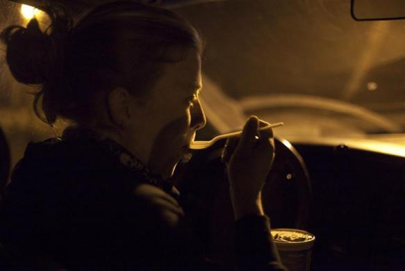 Anna-Rae Douglass, 23, a practicing 'freegan,' eats food that she recently found in a dumpster behind an organic grocery store in Coquitlam, British Columbia, April 5, 2012.