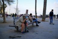 People wearing protective face masks sit on a bench in front of the Barceloneta beach, in Barcelona