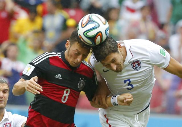Germany's Mesut Ozil (L) fights for the ball with Omar Gonzalez of the U.S. during their 2014 World Cup Group G soccer match at the Pernambuco arena in Recife June 26, 2014. REUTERS/Laszlo Balogh (BRAZIL - Tags: SOCCER SPORT WORLD CUP TPX IMAGES OF THE DAY)