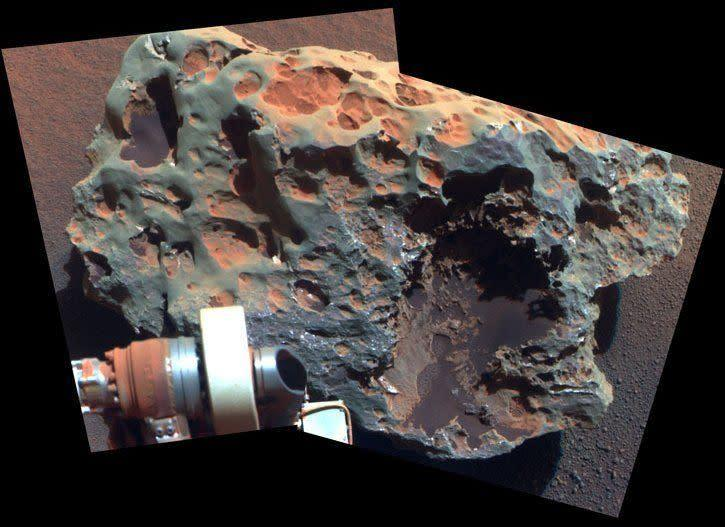 """Opportunity occasionally encounters iron and nickel meteorites while driving across the plains of Meridiani. This Pancam sol 1961 (July 30, 2009) false-color mosaic shows a close up of one called Block Island, which is about 70 cm (28 in) across. <em>From """"Postcards from Mars"""" by Jim Bell; Photo credit: NASA/JPL/Cornell University</em>"""