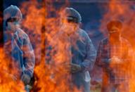 FILE PHOTO: Relatives stand next to the burning pyre of a man who died from the coronavirus disease (COVID-19) during his cremation at a crematorium ground in Srinagar