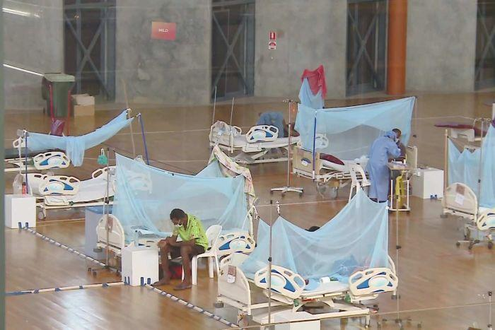 Hospital beds a few metres apart in an indoor sports arena.