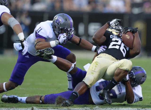 Colorado tailback Tony Jones, front right, is dragged down after a short gain by Central Arkansas linebacker Justin Heard, back right, as defensive back Tirell Wellmaker, left, comes in to cover in the first quarter of a college football game in Boulder, Colo., on Saturday, Sept. 7, 2013. (AP Photo/David Zalubowski)
