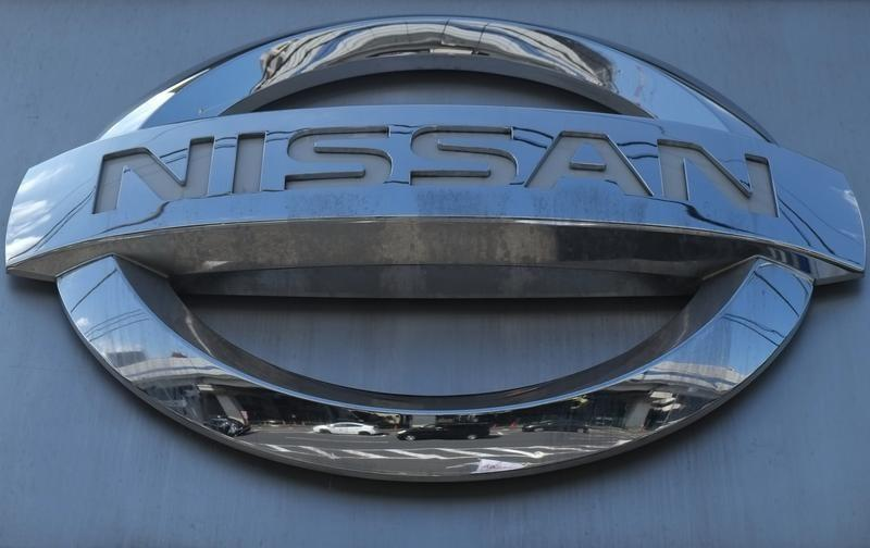 Cars are reflected in a Nissan Motor logo at the company's dealership in Tokyo