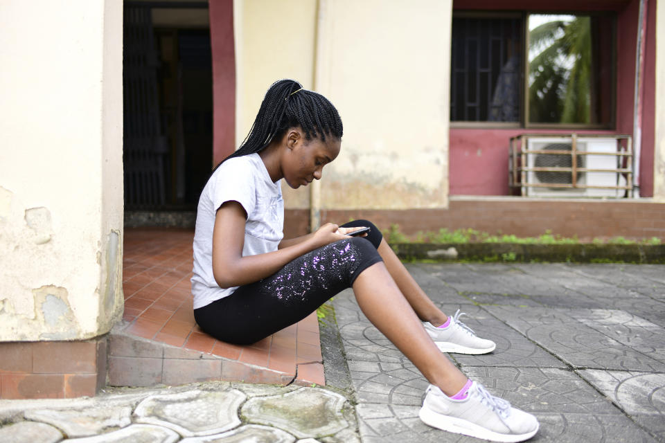 In this photo taken on Wednesday, Oct. 14, 2020, Dodeye Ewa, 16 year old, read a message on her mobile phone outside her house in Calabar, Nigeria. The third child is bothered by President Donald Trump's rhetoric and his policies toward international students, most recently one announced Friday that limits their stays in the U.S. to two or four years with uncertainty about whether their visas will be extended. (AP Photo/Daniel H Williams )