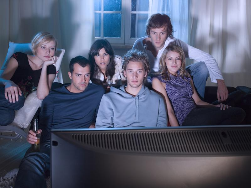 A group of young people sitting on a couch, watching TV.