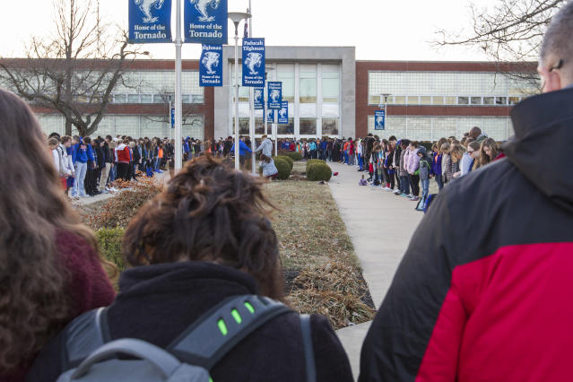 <p>Students and community members hold hands in prayer before classes at Paducah Tilghman High School in Paducah, Ky., Wednesday, Jan. 24, 2018. The gathering was held for the victims of the Marshall County High School shooting on Tuesday. (Photo: Ryan Hermens/The Paducah Sun via AP) </p>