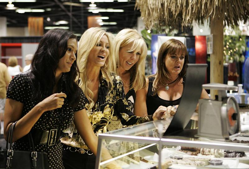 "This undated publicity photo provided by Bravo shows, from left, Jo De La Rosa, Lauri Peterson, Vicki Gunvalson and Jeana Keough in a scene from ""Home and Garden Show"" in Bravo's season two of ""The Real Housewives of Orange County."" Later in 2013, the show will reach a TV milestone: its 100th episode. To mark the occasion, Bravo is planning a standalone two-hour special that will pull back the curtain on the series and revisit past cast members. (AP Photo/Bravo, Kelsey McNeal)"