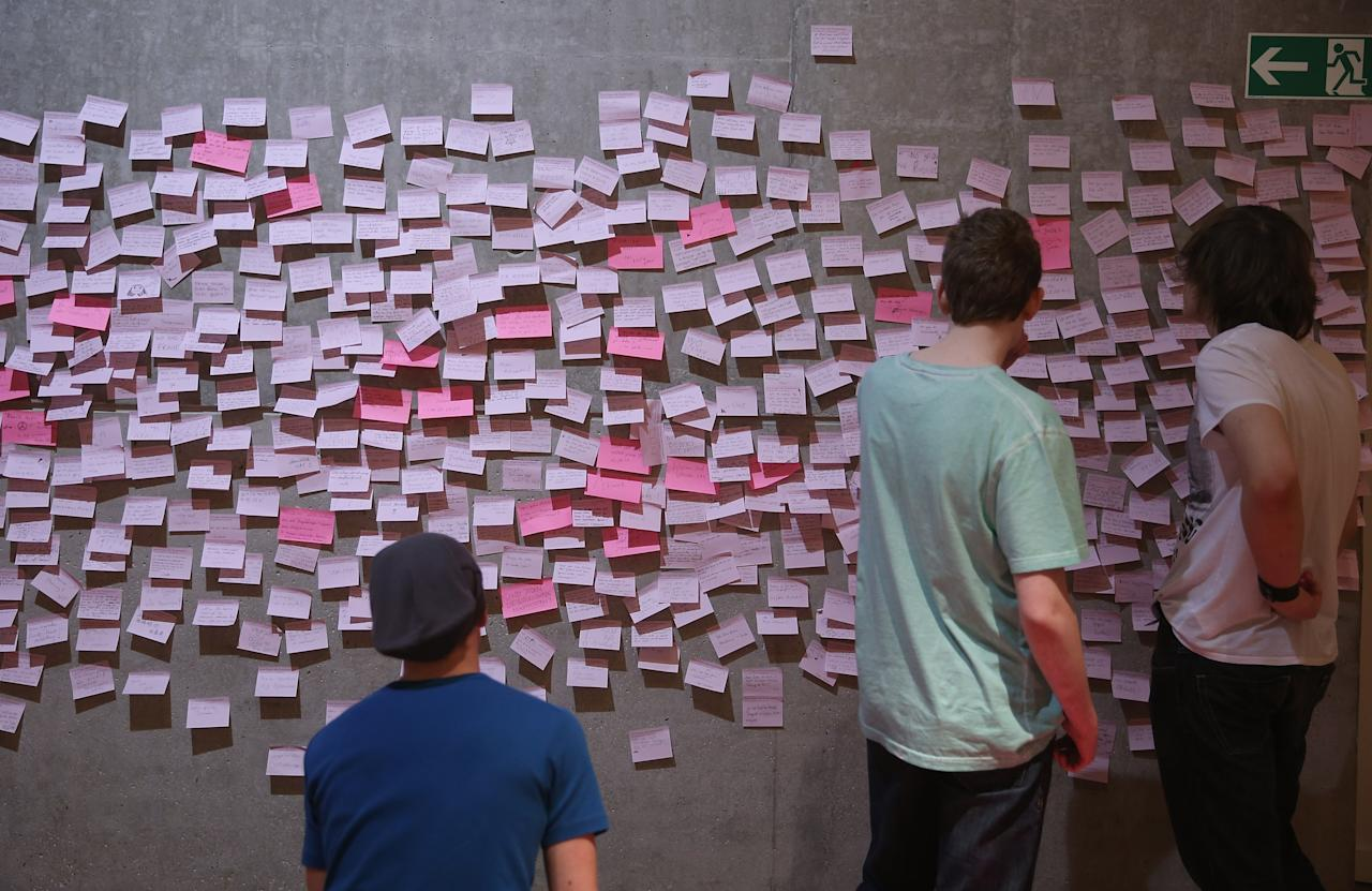"BERLIN, GERMANY - APRIL 04:  Visitors look at comments left by visitors at the exhibition ""The Whole Truth - Everything You Always Wanted To Know About Jews . . . "" at the Juedisches Museum (Jewish Museum) on April 4, 2013 in Berlin, Germany. The exhibition presents every-day aspects of Jewish life, poses simple questions answered with exhibits and challenges certain stereotypes. However its live exhibit, which features a Jewish person who sits in a plastic enclosure open on one side for several hours a day to answer visitors' questions, has sparked criticism from some Jewish groups.  (Photo by Sean Gallup/Getty Images)"