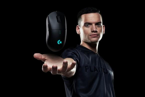 A man holding out his hand with a Logitech wireless gaming mouse hovering above the palm of his hand.