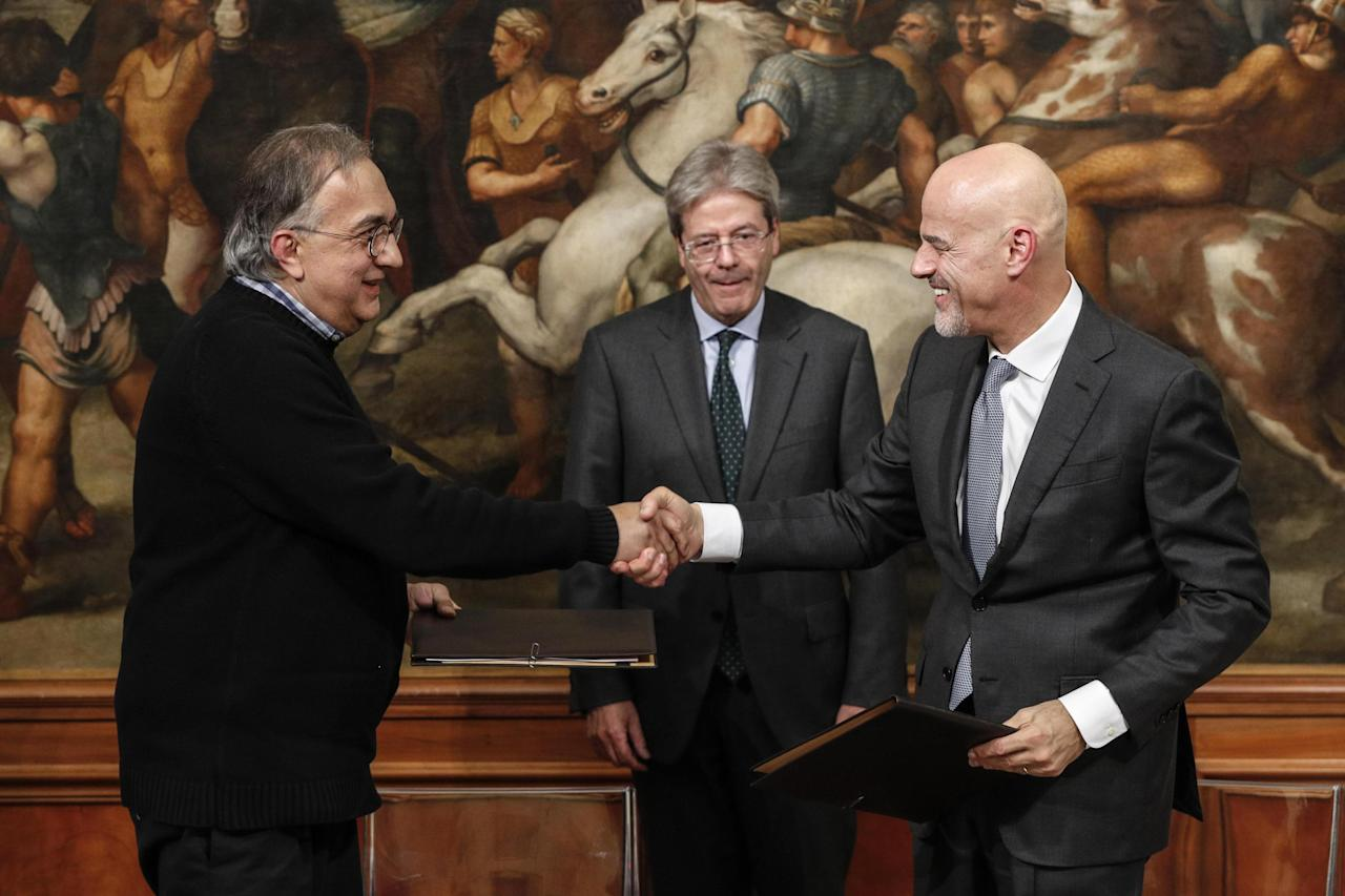 FIAT Chrysler CEO Sergio Marchionne, left, and chief executive of Eni Claudio Descalzi shake hands as Italian Premier Paolo Gentiloni looks at them, at Palazzo Chigi Premier's office in Rome, Tuesday, Nov. 21, 2017. The CEOs of Italian-American carmaker Fiat Chrysler Automobiles SpA and Italian energy giant ENI have agreed to jointly develop technologies to reduce carbon emissions from vehicles. The companies signed the agreement Tuesday in Rome with Premier Paolo Gentiloni that broadly focus on technologies related to compressed natural gas and liquefied natural gas, alternative fuels in which Italy has long been a market leader. (Giuseppe Lami/ANSA via AP)