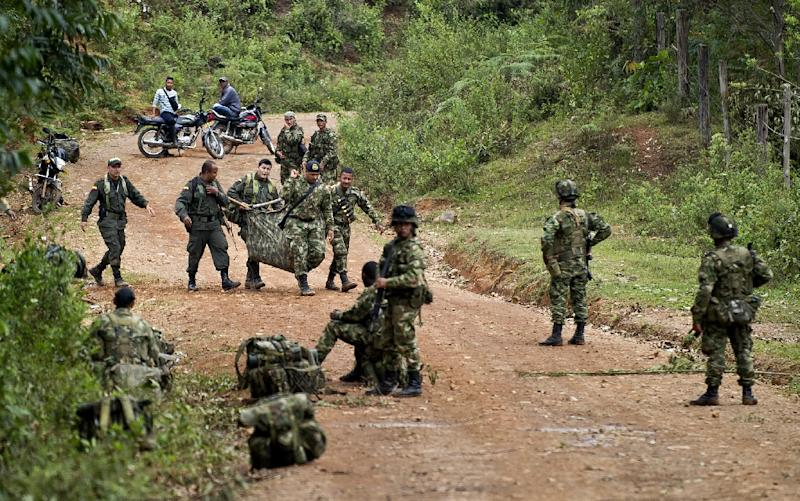 Colombian soldiers carry equipment of one of ten soldiers killed by FARC guerrillas, in the rural area of Buenos Aires, department of Cauca, Colombia, on April 15, 2015 (AFP Photo/Luis Robayo)