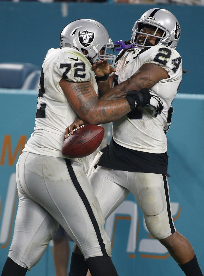 <p>Oakland Raiders offensive tackle Donald Penn (72) lifts running back Marshawn Lynch (24) after Lynch scored a touchdown, during the second half of an NFL football game against the Miami Dolphins, Sunday, Nov. 5, 2017, in Miami Gardens, Fla. (AP Photo/Wilfredo Lee) </p>