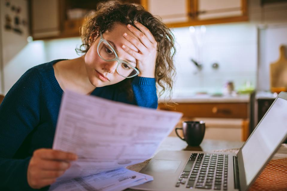 Young woman reading her bill papers, looking stressed