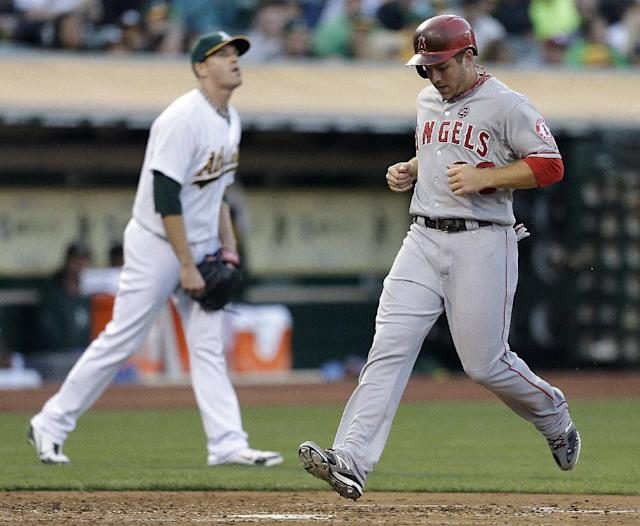 Los Angeles Angels' J.B. Shuck, right, scores past Oakland Athletics pitcher Dan Straily in the third inning of a baseball game on Thursday, July 25, 2013, in Oakland, Calif. Shuck scored on a single by Angels' Albert Pujols. (AP Photo/Ben Margot)